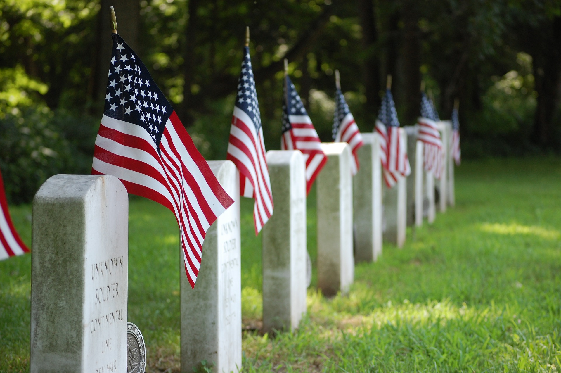 American flags stand guard over each gravestone in a military cemetery